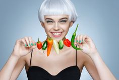Beautiful young girl with different peppers. royalty free stock images