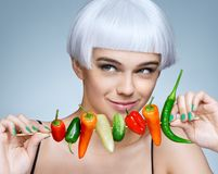 Beautiful young girl with different peppers. Stock Photo