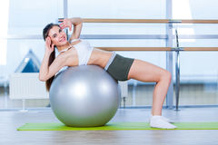 Beautiful young girl doing exercises with fit ball at gym. Stock Photos