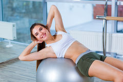 Beautiful young girl doing exercises with fit ball at gym. Royalty Free Stock Images