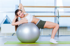 Beautiful young girl doing exercises with fit ball at gym. Royalty Free Stock Photos