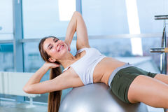 Beautiful young girl doing exercises with fit ball at gym. Stock Images