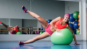 Beautiful young girl doing exercises with fit ball at sport gym. Royalty Free Stock Photo