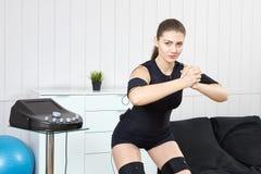 Beautiful girl posing next to muscle stimulation machine prepari. Beautiful young girl doing exercises on the machine for muscle stimulation. Innovative Royalty Free Stock Photos