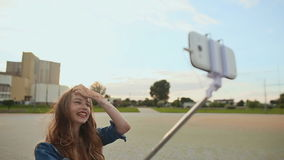 Beautiful young girl doing selfie using selfie stick on a background of the city. Beautiful young girl doing selfie using selfie stick on a background of the stock video