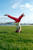 Beautiful young girl doing stretching exercise on green grass. Stock Photo