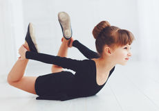 Beautiful young girl doing stretching exercises at ballet school Stock Photos