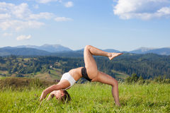 Beautiful young girl doing yoga exercise. At the summer meadow royalty free stock images