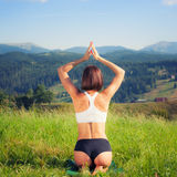 Beautiful young girl doing yoga exercise. At the summer meadow Stock Image