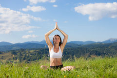 Beautiful young girl doing yoga exercise. At the summer meadow stock photos