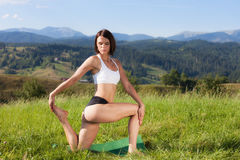 Beautiful young girl doing yoga exercise. At the summer meadow Stock Photography
