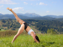 Beautiful young girl doing yoga exercise. At the summer meadow Royalty Free Stock Photo