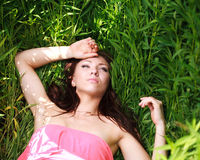 Beautiful young girl dreams, lying on green grass Royalty Free Stock Image