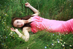Beautiful young girl dreams, lying on the meadow Stock Photo