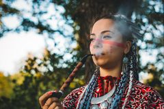 Beautiful young girl in a dress of Native Americans smoking pipe. Close up royalty free stock photos