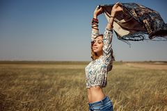 Beautiful young girl dressed in hippie style in a wheat field stock photos