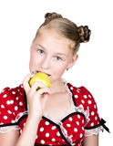 Beautiful young girl dressed in a red dress with white polka dots eating an apple. healthy food - strong teeth concept Stock Image