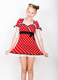Beautiful young girl dressed in a red dress with white polka dots. Funny kids pamper and posing Royalty Free Stock Image