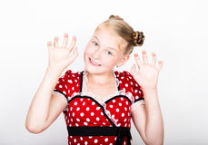 Beautiful young girl dressed in a red dress with white polka dots. Funny kids pamper and posing Royalty Free Stock Images
