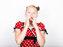Beautiful young girl dressed in a red dress with white polka dots. Funny kids pamper and posing Stock Images