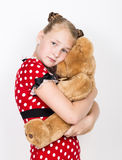 Beautiful young girl dressed in a red dress with white polka dots holding a teddy bear Royalty Free Stock Photo