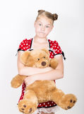 Beautiful young girl dressed in a red dress with white polka dots holding a teddy bear Royalty Free Stock Photography