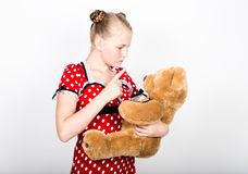 Beautiful young girl dressed in a red dress with white polka dots holding a teddy bear Royalty Free Stock Image