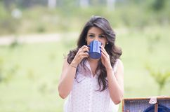 Beautiful young girl drinking coffee in a field Stock Photo