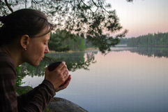 Beautiful young girl drinking cup of coffee or tea to warm up. Portrait attractive woman thoughtfully looks out over lake with wat Royalty Free Stock Photos