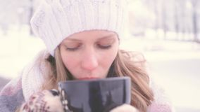 Beautiful young girl drinking hot chocolate ouenjoy outside in the park smell good and keeping warm concept of coziness. Of comfort. 4k UHD 3840 2160 slow stock footage