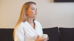 Beautiful young girl drinking tea in relaxation room after Spa treatments stock video footage