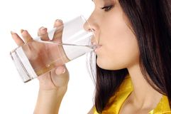 Beautiful young girl drinks water from glass Stock Photo