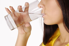 Beautiful young girl drinks water from glass royalty free stock image