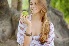 Beautiful young girl eating green apple Royalty Free Stock Image