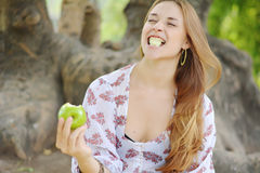 Beautiful young girl eating green apple Royalty Free Stock Images
