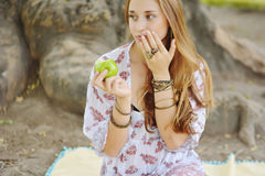 Beautiful young girl eating green apple Stock Photography