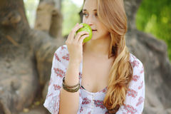 Beautiful young girl eating green apple Royalty Free Stock Photography