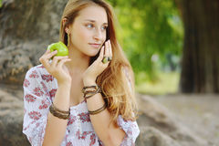 Beautiful young girl eating green apple Stock Images