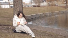 Beautiful young girl eating a red Apple in the Park under a tree near the water and reading a book stock footage