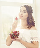 Beautiful and young girl eating strawberries Stock Photography