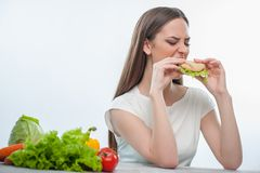 Beautiful young girl is eating unhealthy food Stock Images