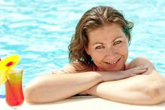 A beautiful young girl at the edge of the pool smiling Royalty Free Stock Images