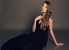Beautiful young girl in elegant black dress with bijou Stock Images