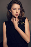 Beautiful young girl in elegant black dress with bijou Stock Image