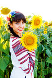 Beautiful young girl in embrodery holding a sunflower on a  plan Royalty Free Stock Photo