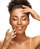 Beautiful young girl enjoying her clean skin. Photo of african american girl with perfect skin isolated on white background. Beauty & Skin care concept stock photos