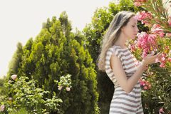 Beautiful young girl enjoying the scent of flowers. In a scenic garden in a sunny summer day royalty free stock image