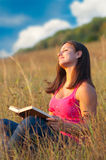 Beautiful young girl enjoys sun on the meadow Stock Photos