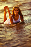 Beautiful young girl enjoys the sun and the ocean. Royalty Free Stock Photography