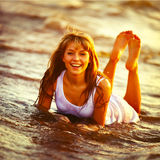 Beautiful young girl enjoys the sun and the ocean. Royalty Free Stock Image